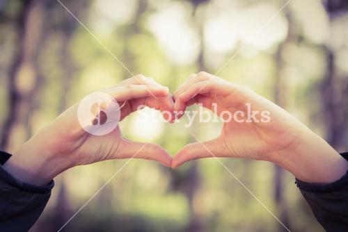 Carefree female hiker framing heart with hands