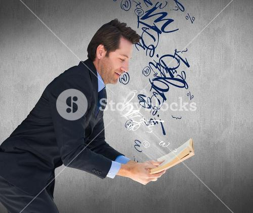 Composite image of businessman lying on the floor while reading a book