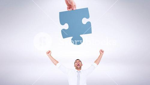 Composite image of hand holding jigsaw piece