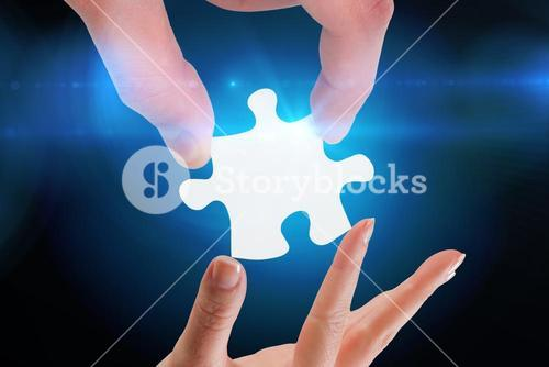 Composite image of hands holding jigsaw
