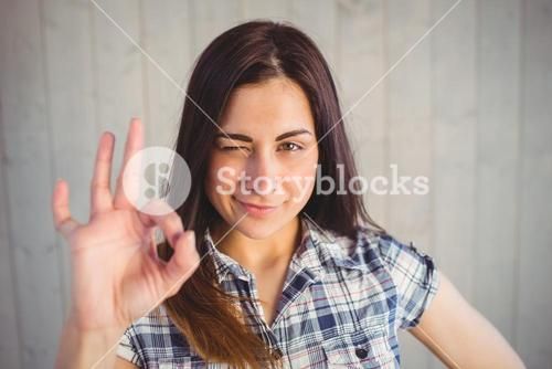 Pretty hipster making ok sign with hand