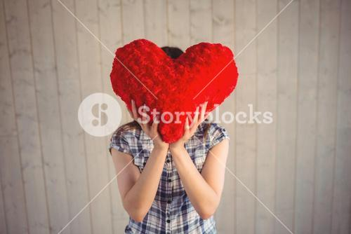 Pretty hipster holding heart pillow