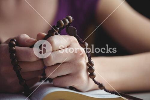 Woman praying with her bible and rosary beads