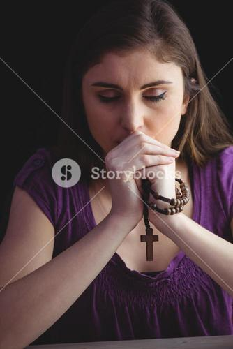Woman praying with wooden rosary beads