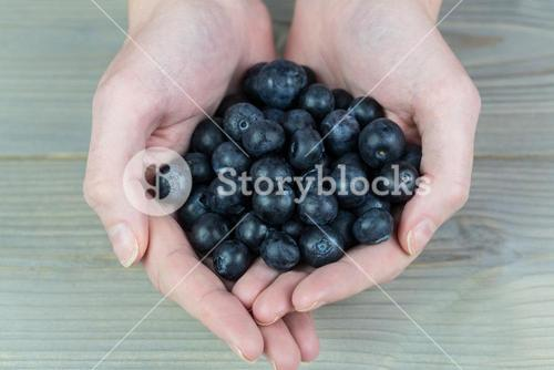 Woman showing handful of blueberries
