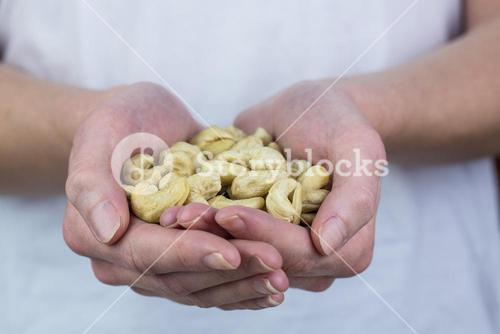 Woman showing handful of cashews