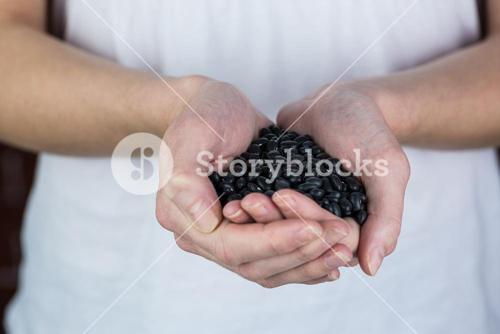 Woman showing handful of black beans