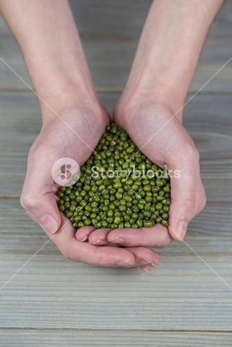 Woman showing handful of lentils