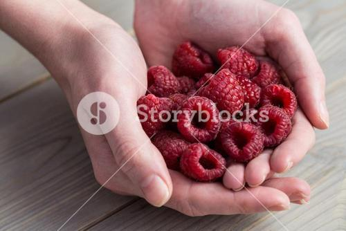 Woman showing handful of raspberries
