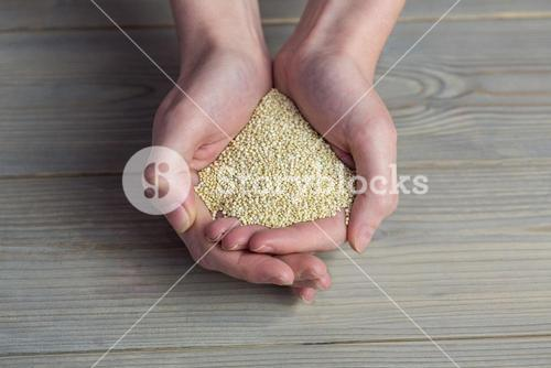 Woman showing handful of sesame seed