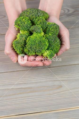 Woman showing fresh green brocolli