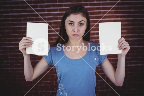 Pretty brunette holding two pages
