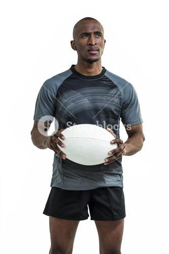 Thoughtful sportsman holding rugby ball