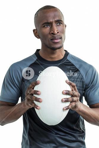 Thoughtful athlete holding rugby ball
