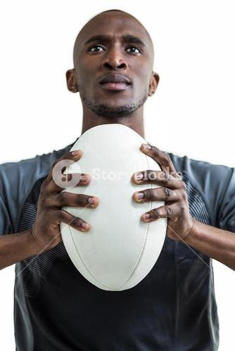 Cropped image of sportsman pressing rugby ball while looking up