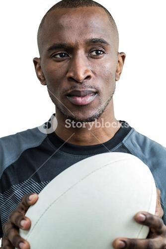 Close-up of athlete thinking while holding rugby ball