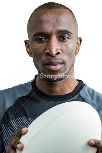 Close-up of thoughtful athlete holding rugby ball