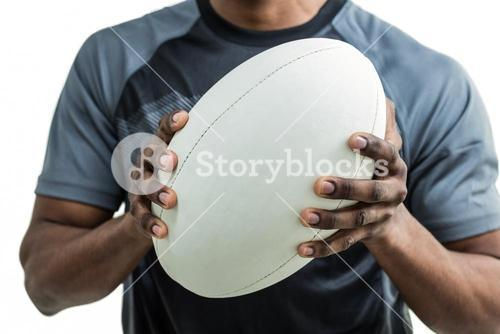 Mid section of sportsman holding rugby ball