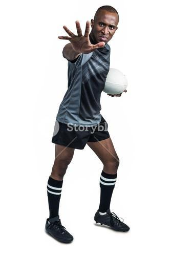 Portrait of sportsman gesturing while standing with rugby ball