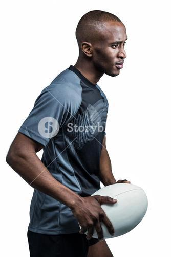 Confident sportsman with rugby ball