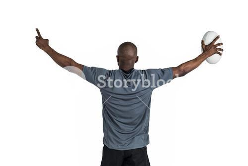 Rear view of sportsman with arms raised holding rugby ball