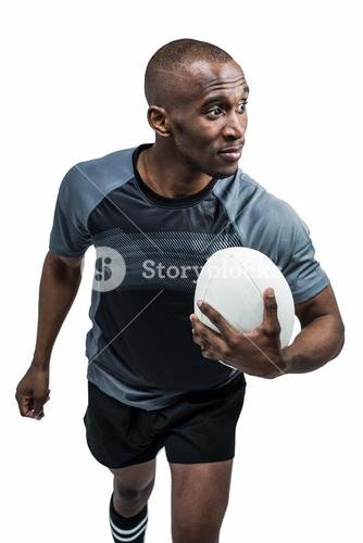 Confident athlete with rugby ball