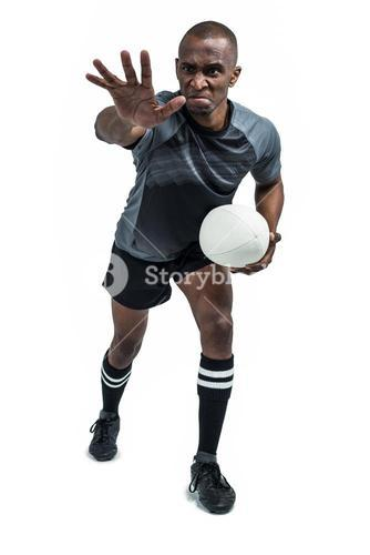 Aggressive rugby player gesturing while holding ball