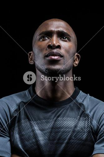Thoughtful athlete against black background