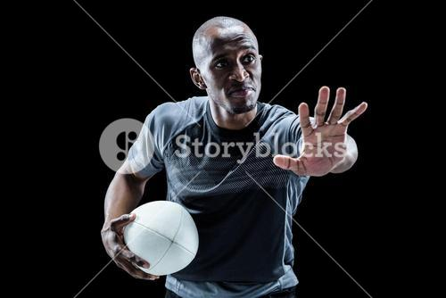 Serious sportsman gesturing while holding rugby ball