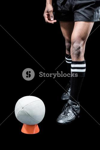 Rugby ball on kicking tee by sportsman