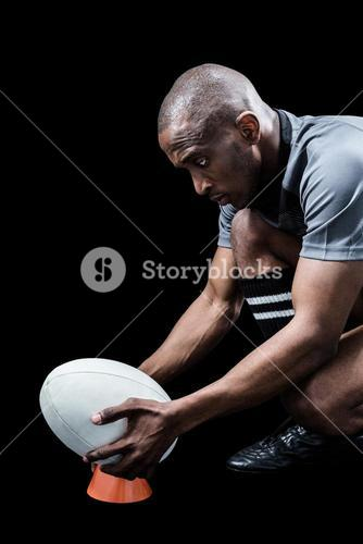 Sportsman keeping rugby ball on kicking tee