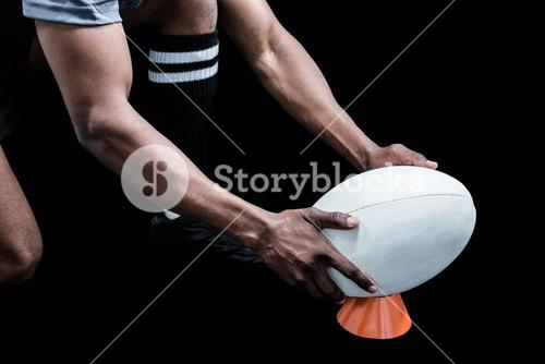 Cropped image of sportsman keeping rugby ball on kicking tee