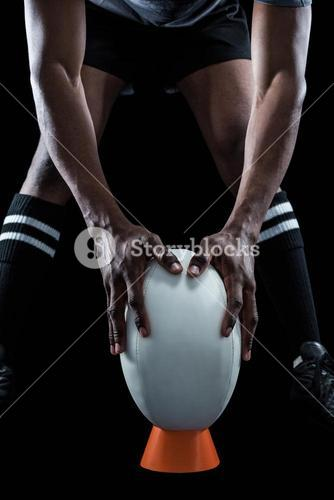 Mid section of rugby player keeping ball on kicking tee