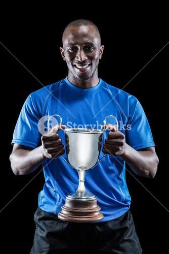 Portrait of happy athlete holding trophy