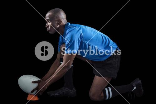 Confident rugby player looking away while keeping ball on kicking tee