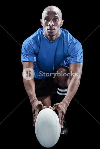 Portrait of rugby player holding ball while kneeling