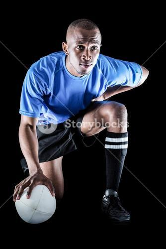 Serious rugby player kneeling while holding ball