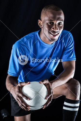 Portrait of rugby player with ball smiling while kneeling