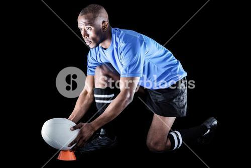 Rugby player looking away while keeping ball on kicking tee
