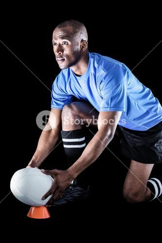 Sportsman looking away while keeping rugby ball on kicking tee