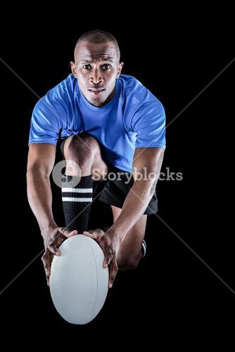 Portrait of rugby player kneeling and holding ball