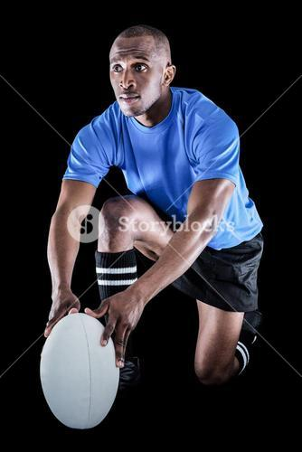 Rugby player holding ball while kneeling