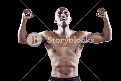 Happy shirtless athlete cheering with clenched fist