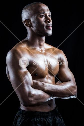 Shirtless athlete standing with arms crossed while looking away