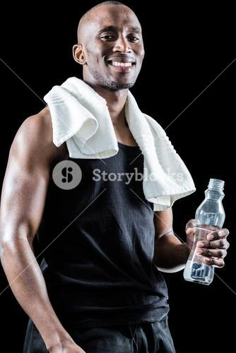 Portrait of happy muscular man with towel around neck holding bottle