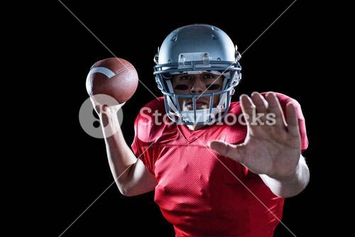 Portrait of sportsman defending while holding American football