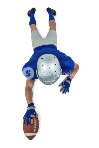 Full length rear view of American football player reaching towards ball