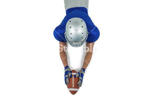 Rear view of American football player reaching towards ball