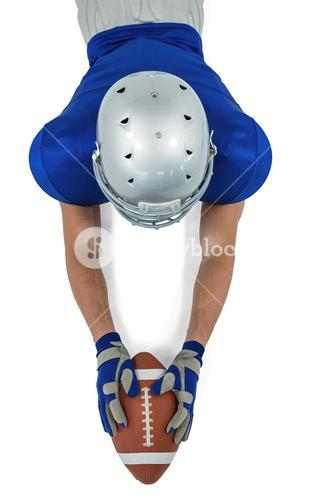 High angle view of American football player reaching towards ball