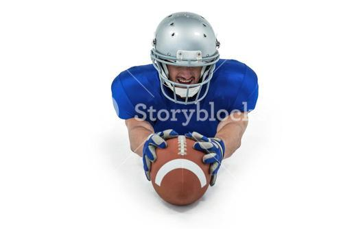 American football player reaching towards ball